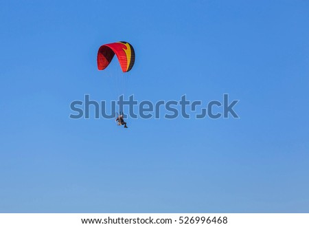 paraglider fly with paramotor flying on blue sky background