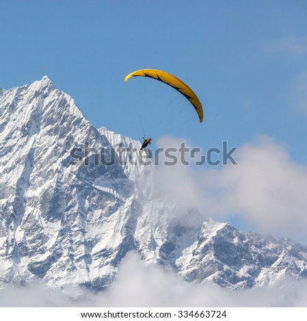 Paraglider flying against the mountain Lhotse (8516 m) - Everest region, Nepal, Himalayas