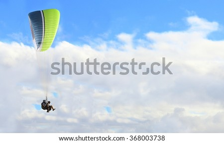 Paraglider flying on bright blue day with white puffy clouds - stock photo