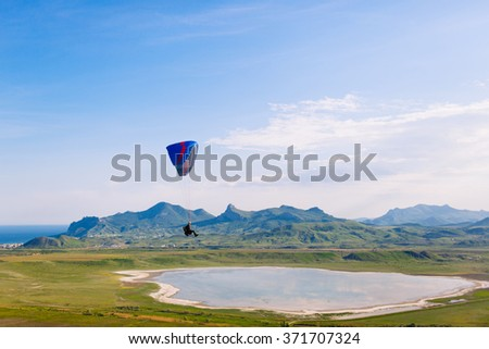 Paraglider flying over a lake with mountains in background - stock photo