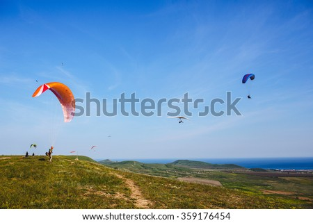 Paraglider flying over mountains in summer day. Paraglider prepares for flight - stock photo