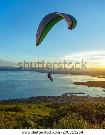 Paraglider flying over Petropavlovsk-Kamchatsky and Avacha Bay on the background of the cone of the volcano Karyaksky at sunset - Kamchatka, Russia - stock photo