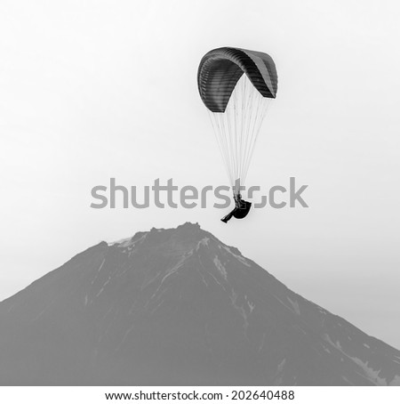 Paraglider flying over Petropavlovsk-Kamchatsky on the background of the cone of the volcano Koryaksky at sunset - Kamchatka, Russia (black and white) - stock photo