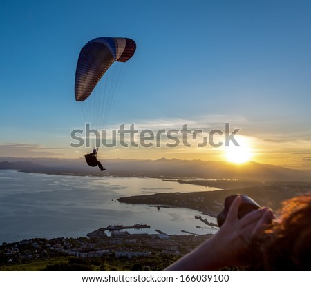 Paraglider flying over vespers Petropavlovsk-Kamchatsky on the background of the Avachinsky bay at sunset - Kamchatka, Russia