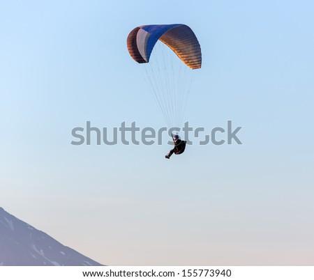 Paraglider flying over vespers Petropavlovsk-Kamchatsky on the background of the slope of volcano Koryaksky at sunset - Kamchatka, Russia - stock photo