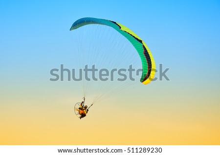 paraglider in flight in blue sky