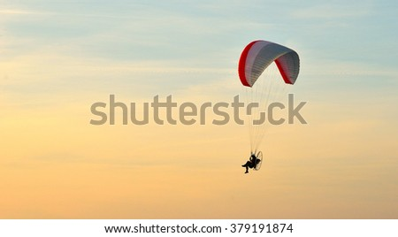 Paraglider in flight  in summer at sunset - stock photo