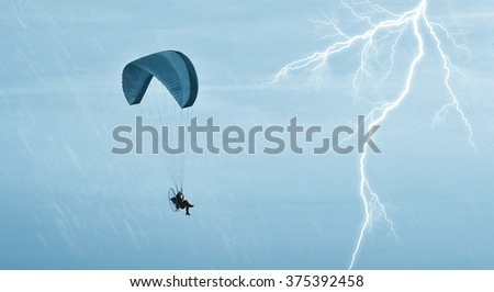 Paraglider in flight in the storm in autumn - stock photo