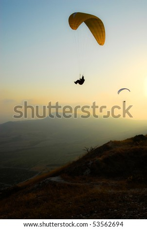 Paraglider in the evening sky - stock photo