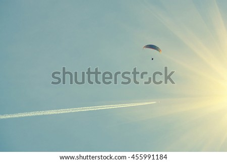 Paraglider in the sunny sky with a trace of an airplane - stock photo