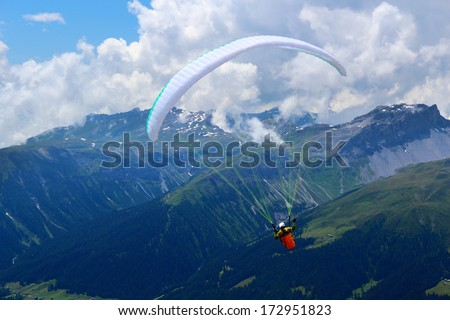 Paraglider is flying in front of mountain landscape of Swiss Alps, Jacobshorn, Davos, Switzerland