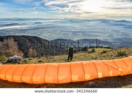 Paraglider is waiting for the right wind to start his flight. Looking at beautiful valley below with clouds and mist. - stock photo