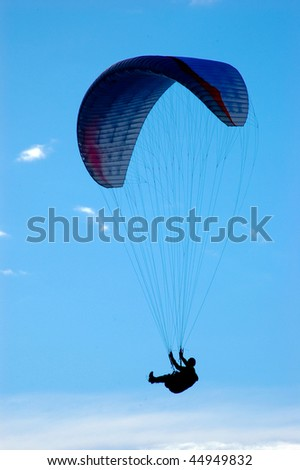 Paraglider on clean blue sky vertical - stock photo