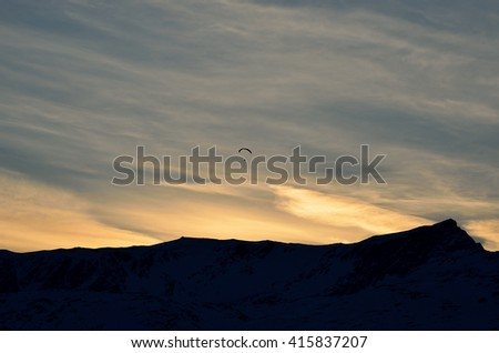 paraglider over snow covered mountain with bright and colourful dawn light