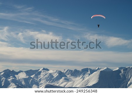 Paraglider over snow mountains - stock photo