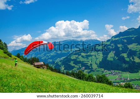 Paraglider preparing for flight over the green alpine meadows, Austria - stock photo