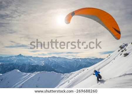 Paraglider running on snowy slope for take off with bright orange kite. Stunning background of the italian Alps in winter season. Shot taken in backlight, unrecognizable person. - stock photo