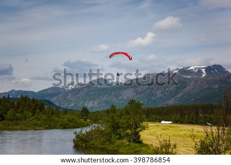 Paraglider silhouette flying over Norway mountains - stock photo