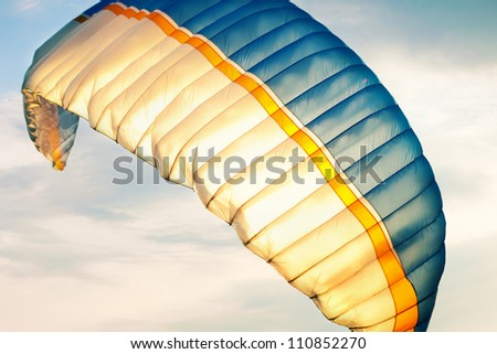 paraglider wing in air against sky - stock photo