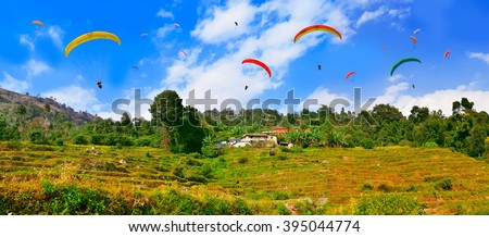 Paragliders flying over the Himalayas and rice fields , Pokhara , Nepal - stock photo