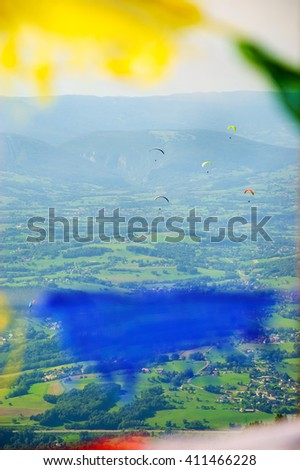 Paragliders flying over valley (Alps mountains at background) seen through the unfocused colorful flags waving in the wind. Annecy lake area (Haute-Savoie, France).  - stock photo