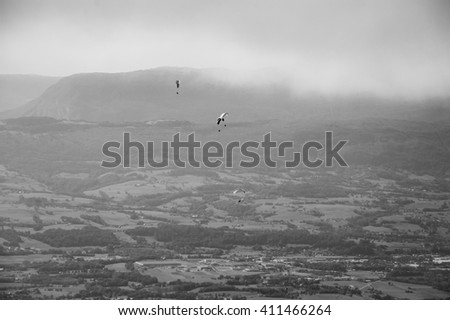 Paragliders group flying over valley and Alps mountains at background. Annecy lake area (Haute-Savoie, France). Aged photo. Black and white. - stock photo