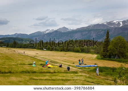 Paragliders group is preparing for flight over the mountains in Norway - stock photo