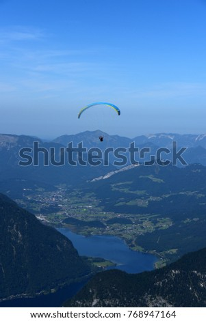 paragliders in the blue sky above Austrian Alps and Hallstatt Lake