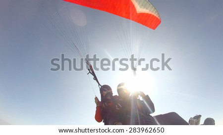 Paragliding against sunshine - stock photo