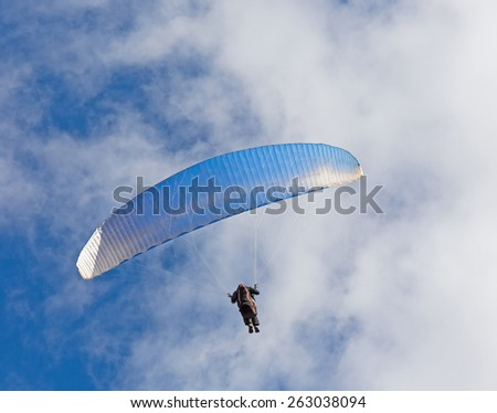 Paragliding against the blue and white skies - stock photo