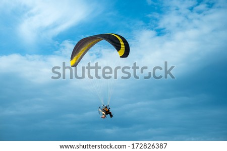 Paragliding fly on blue cloudy sky