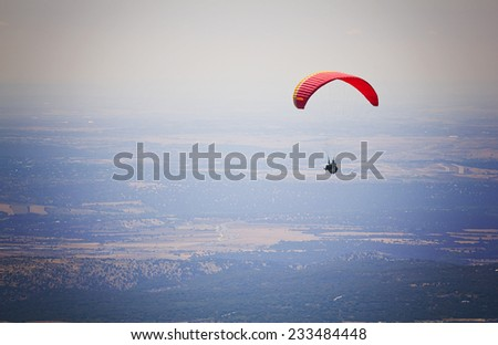 Paragliding, flying over El Escorial in Madrid, Spain. - stock photo