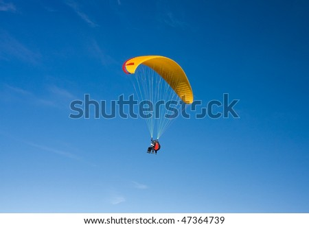 Paragliding in Bulgaria over the mountains against clear blue sky