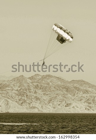 Paragliding in the clear sky above the Red Sea - Eilat, Israel (stylized retro) - stock photo