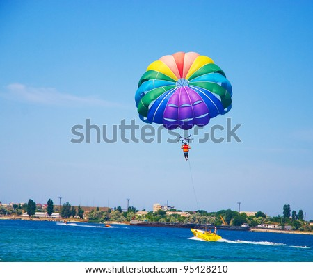 paragliding in the clear sky above the sea - stock photo