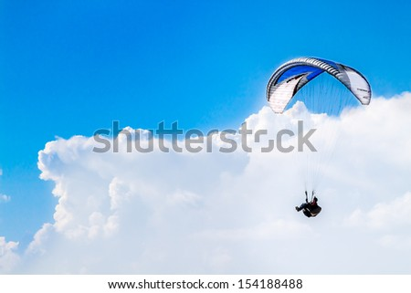 Paragliding on a clear day - stock photo