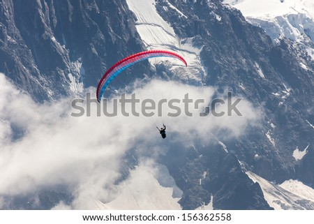 paragliding on the back of high alpine mountains - stock photo