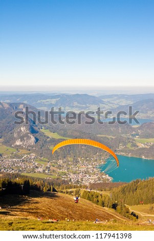 Paragliding over mountains and  Wolfgangsee lake in austrian Alps - stock photo