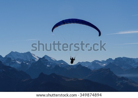 Paragliding over snow-clad mountains - stock photo