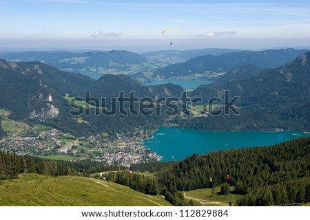 Paragliding over the alps near the town of st.Gilgen at the Wolfgangsee in Austria - stock photo