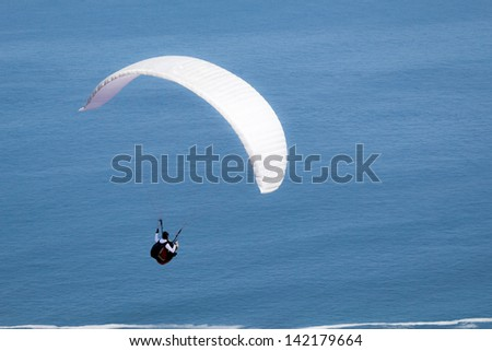 Paragliding over the ocean - stock photo