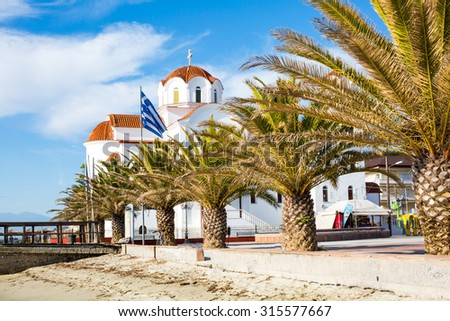 Paralia Katerini, Greece - Aril, 30, 2015: Greek orthodox Church in Paralia Katerini, wooden pier, palm trees and sandy beach, Greece