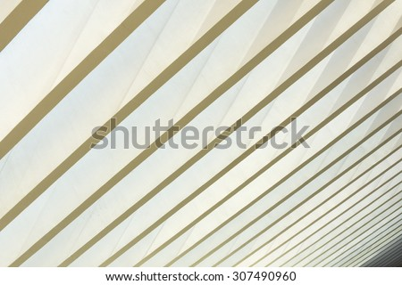 Parallel beams of unique geometrical architectural style ceiling allows natural light to penetrate - stock photo