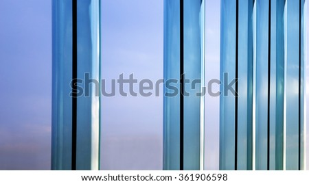 """Parallel metal frames of several neighboring windows and bright sky outside. Unusual closeup photo of modern glass architecture. Metaphor of """"window of opportunity"""" or """"getting out of comfort zone"""" - stock photo"""