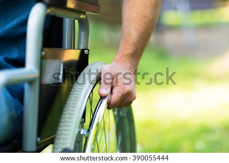 Paralyzed man using his wheelchair - stock photo