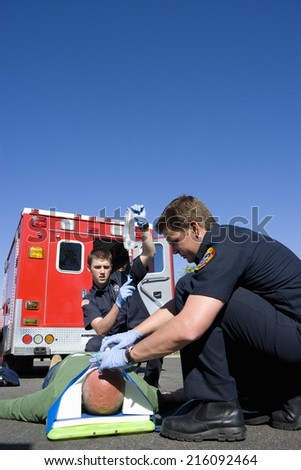 Paramedic and colleague helping man on stretcher by ambulance, low angle view - stock photo
