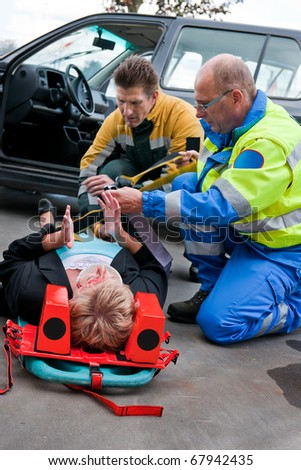 Paramedic and firefighting providing first aid to an injured woman on a stretcher - stock photo