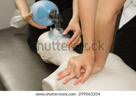 Paramedic practicing Cardiopulmonary resuscitation, CPR on a dummy - stock photo