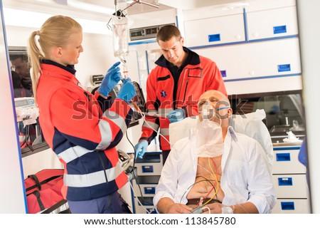 Paramedic putting oxygen mask on patient ambulance sick emergency - stock photo