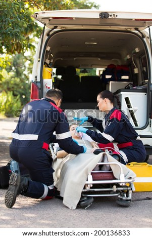 Paramedic putting oxygen mask on unconscious patient